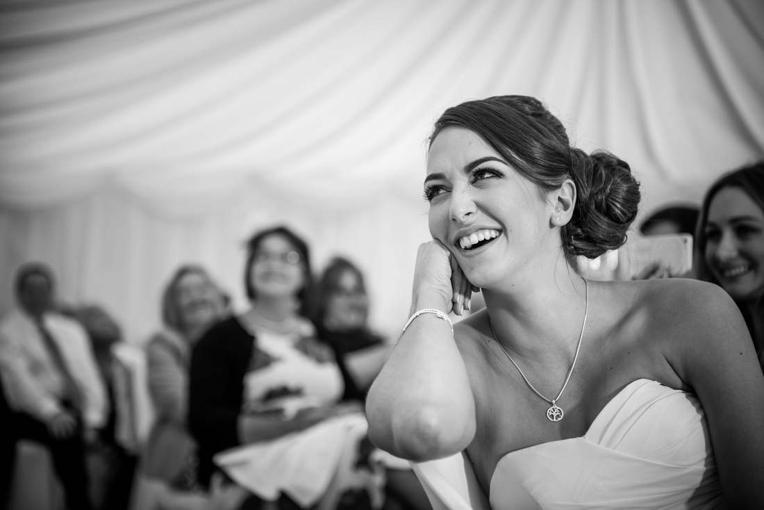 Black and white image of one of the bridesmaids enjoying the speeches during a wedding at Pentre Mawr.
