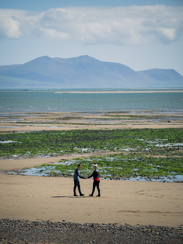Photograph of Liz & Jason on the beach at Newborough Forest & Warren in Anglesey on their pre wedding shoot.  Mountains & estuary in the background, photographed by Celynnen Photography.