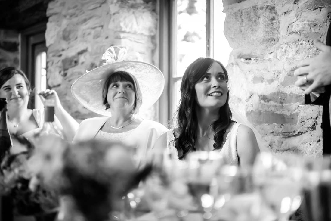 Black and white image of the bride and her mother listening to the groom's speech at a wedding at Plas Isaf.