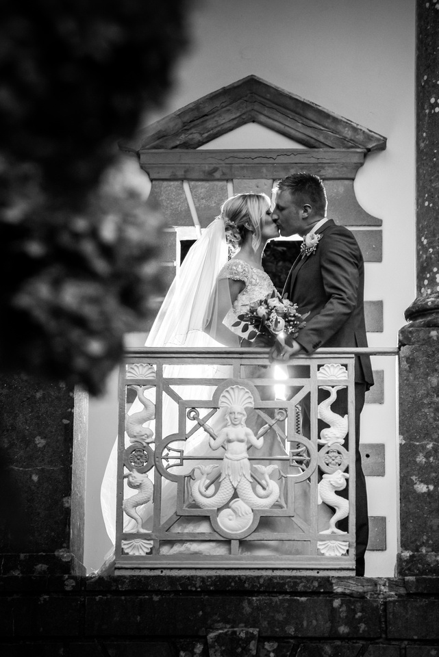 Black and white picture of the bride and groom sharing a kiss on a balcony in Portmeirion.