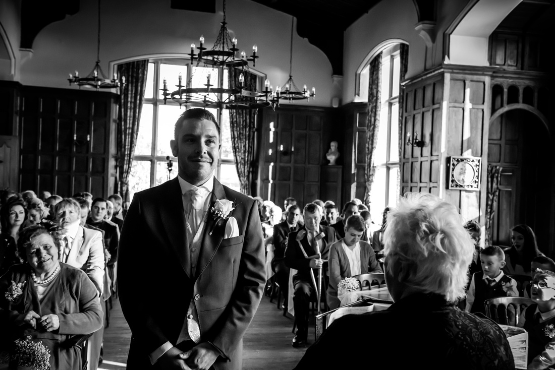 Black and white picture of the groom waiting for his bride at a wedding at Chateau Rhianfa.