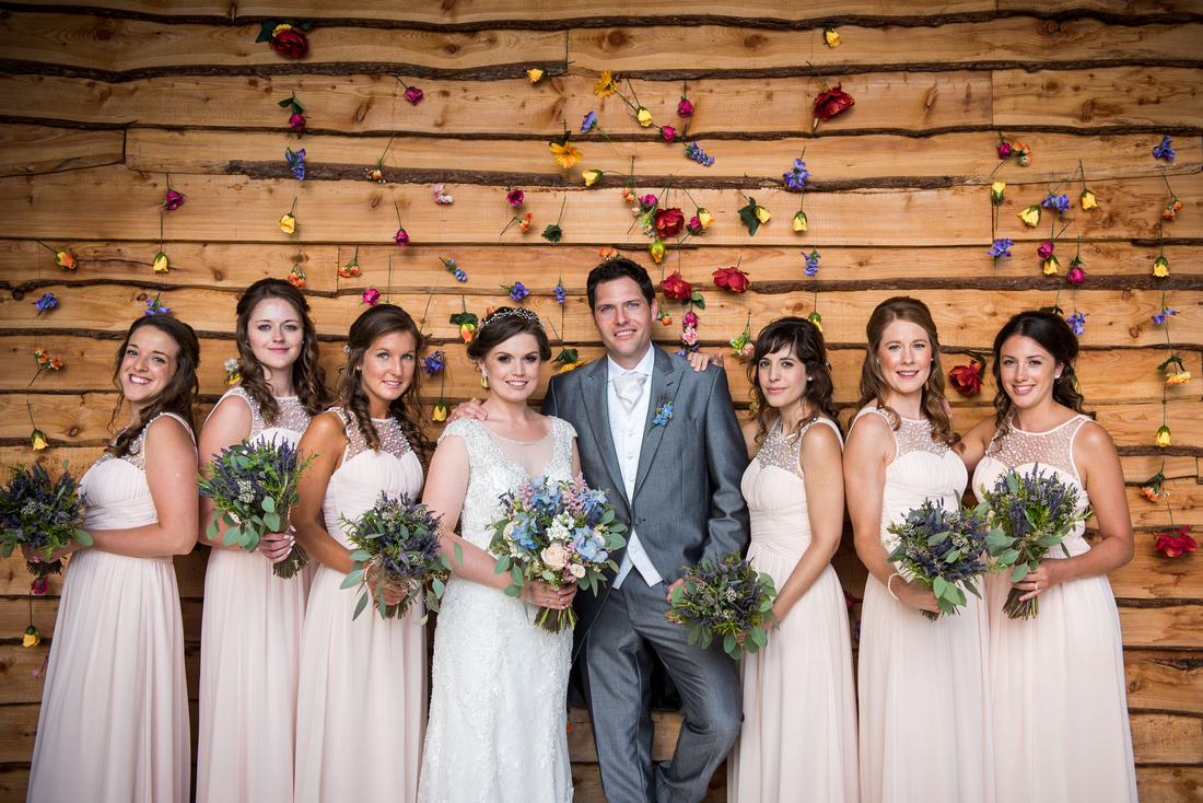 Colourful image of the bride and groom with all of their bridesmaids at the wedding venue Tower Hill Barns.