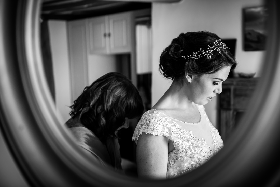 Black and white image of a reflection in a mirror of the mother of the bride helping the bride get ready for her wedding day at Tower Hill Barns.