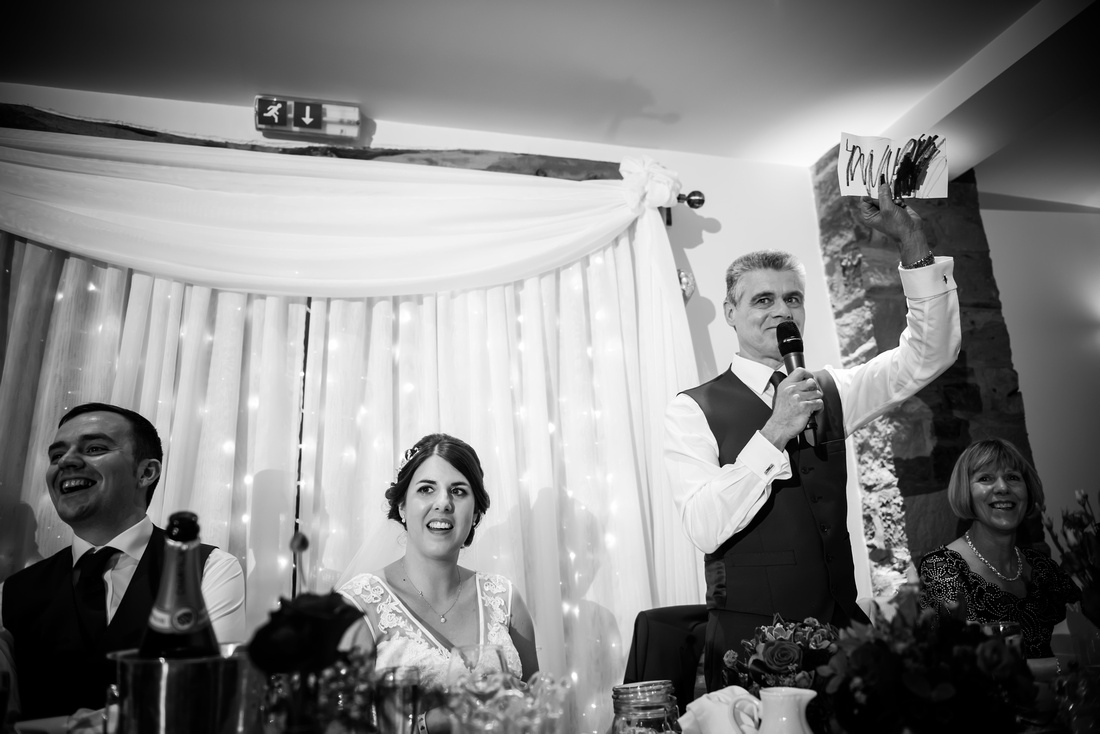 Blak and white image of the father of the bride giving his speech during the wedding reception at Beeston Manor.